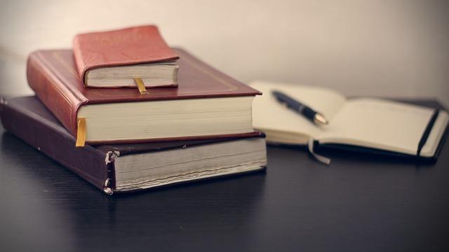 机に積まれた本と開かれたノート
