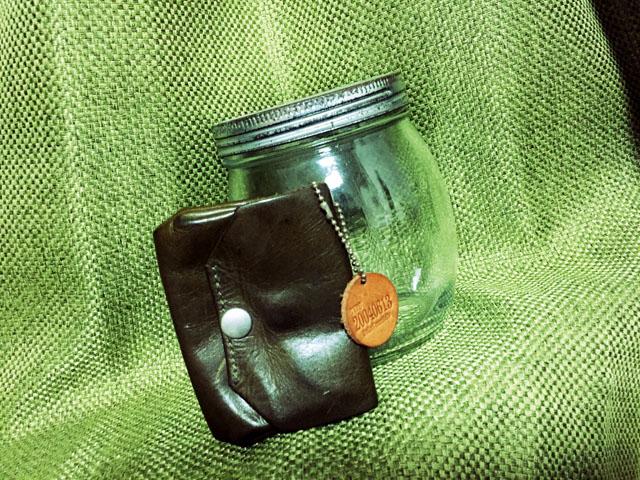処分した革製の小銭入れと100円ショップで購入した小銭貯金用のビン
