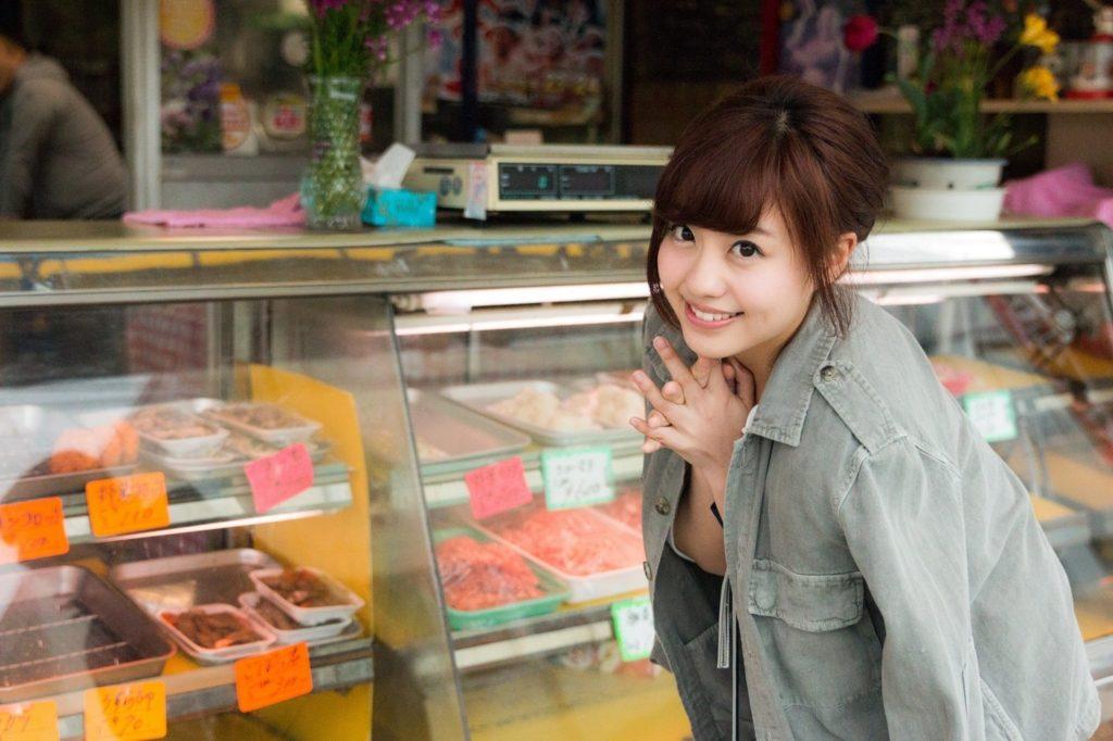 お肉屋さんの前で笑顔でこちらを見つめている女性
