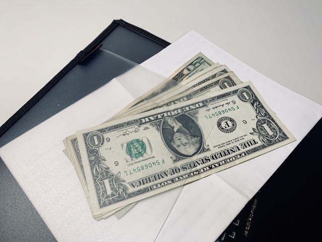 内ポケットに挟まれた資料とドル紙幣
