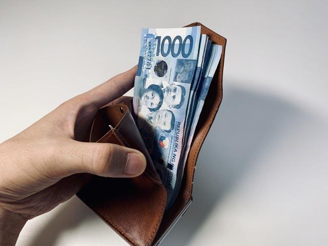 小さい財布にフィリピンペソを折らずに入れている様子