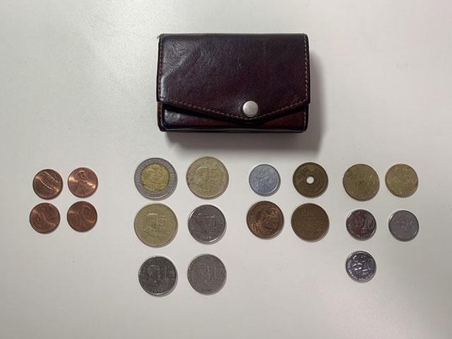 財布と15枚のコインが並んで置かれている