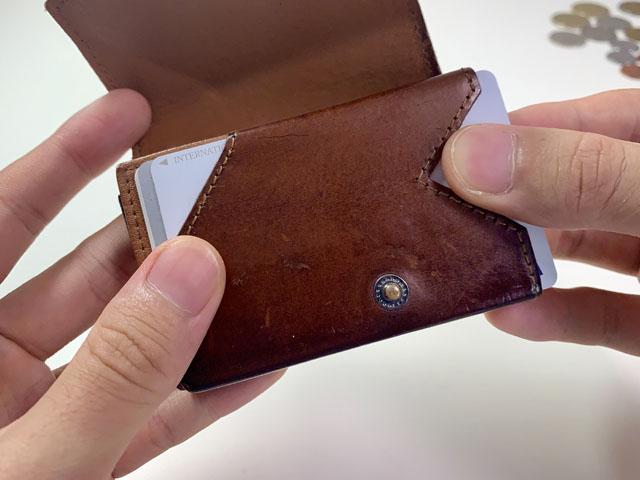小さい財布からカードを取り出す図