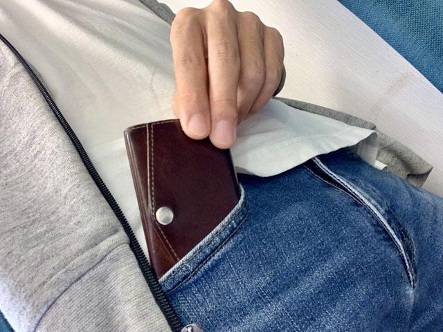 ジーンズのポケットに小さい財布を入れているところ